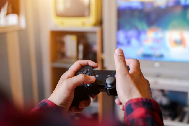 A person holding video game remote in front of tv