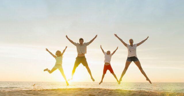 Family doing star jumps on beach
