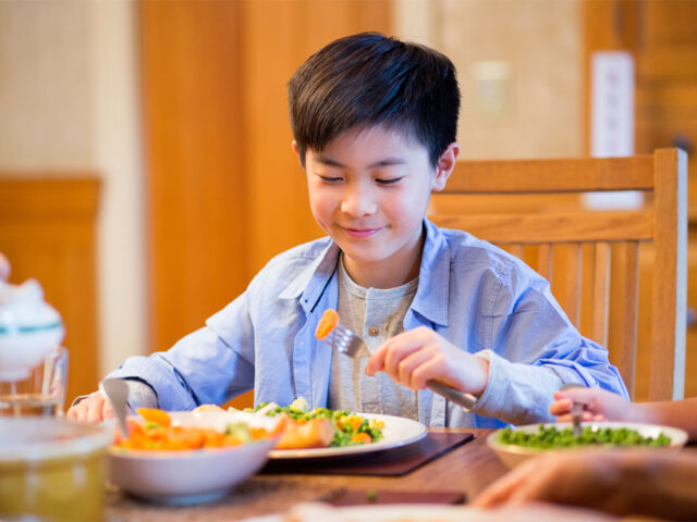 A boy eating aa food at dinning table
