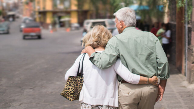 A old couple holding each other and walking on road