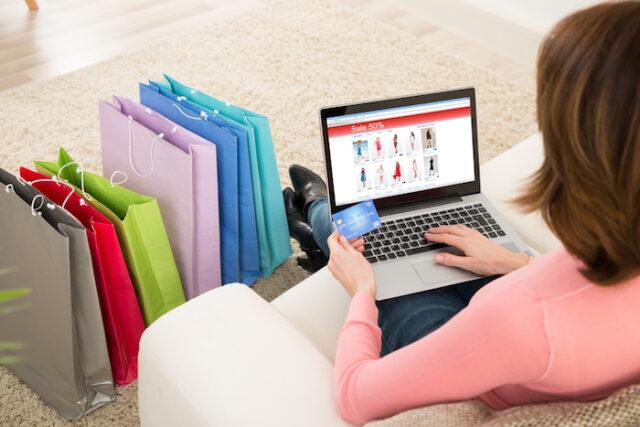 A girl sitting on sofa and hold the laptop, credit card and shopping near to sofa